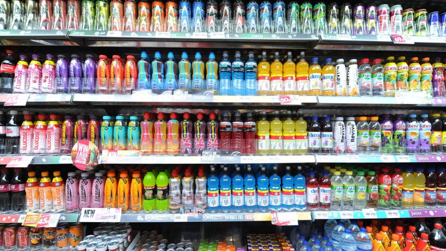 Fizzy carbonated soft drinks for sale in a shop. Sugary fizzy drinks cause diabetes, tooth decay and heart disease.